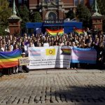 """A similar group image of people hold a banner that reads, """"The Students, Staff, and Faculty of Johns Hopkins Support All Transgender, Intersex, and Gender Minority Members of our Community"""""""