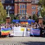 """A group of people hold a banner that reads, """"The Students, Staff, and Faculty of Johns Hopkins Support All Transgender, Intersex, and Gender Minority Members of our Community"""""""