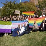 A group of people hold pride flags
