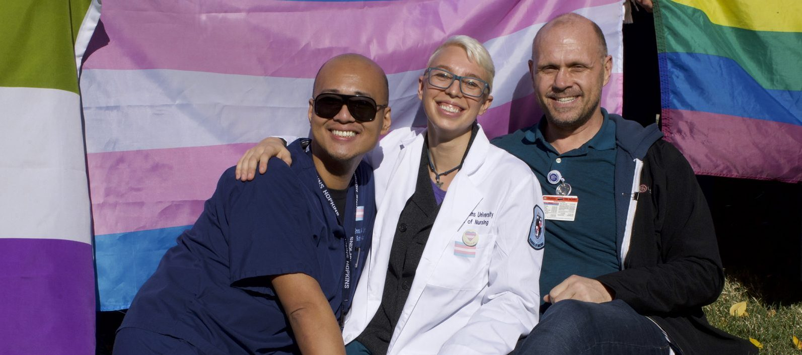 three people in front of the trans flag
