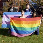 Four people hold the trans and pride flags