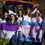 A group of people hold the trans flag, genderqueer flag, and pride flag