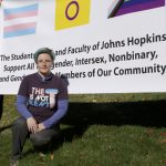 """One person stands infront of a banner that reads, """"The Students, Staff, and Faculty of Johns Hopkins Support All Transgender, Intersex, and Gender Minority Members of our Community"""""""