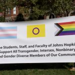 """Two people hold a banner that reads """"The Students, Staff, and Faculty of Johns Hopkins Support All Transgender, Intersex, and Gender Minority Members of our Community"""""""