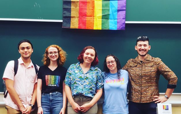 Five students standing under a rainbow flag.