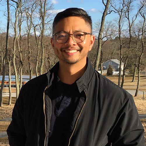 michael in black jacket, short hair with glasses in rural setting