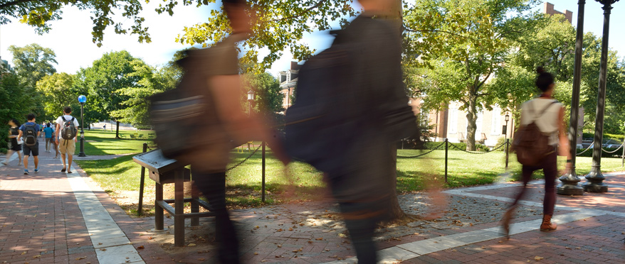Students walking quickly across campus