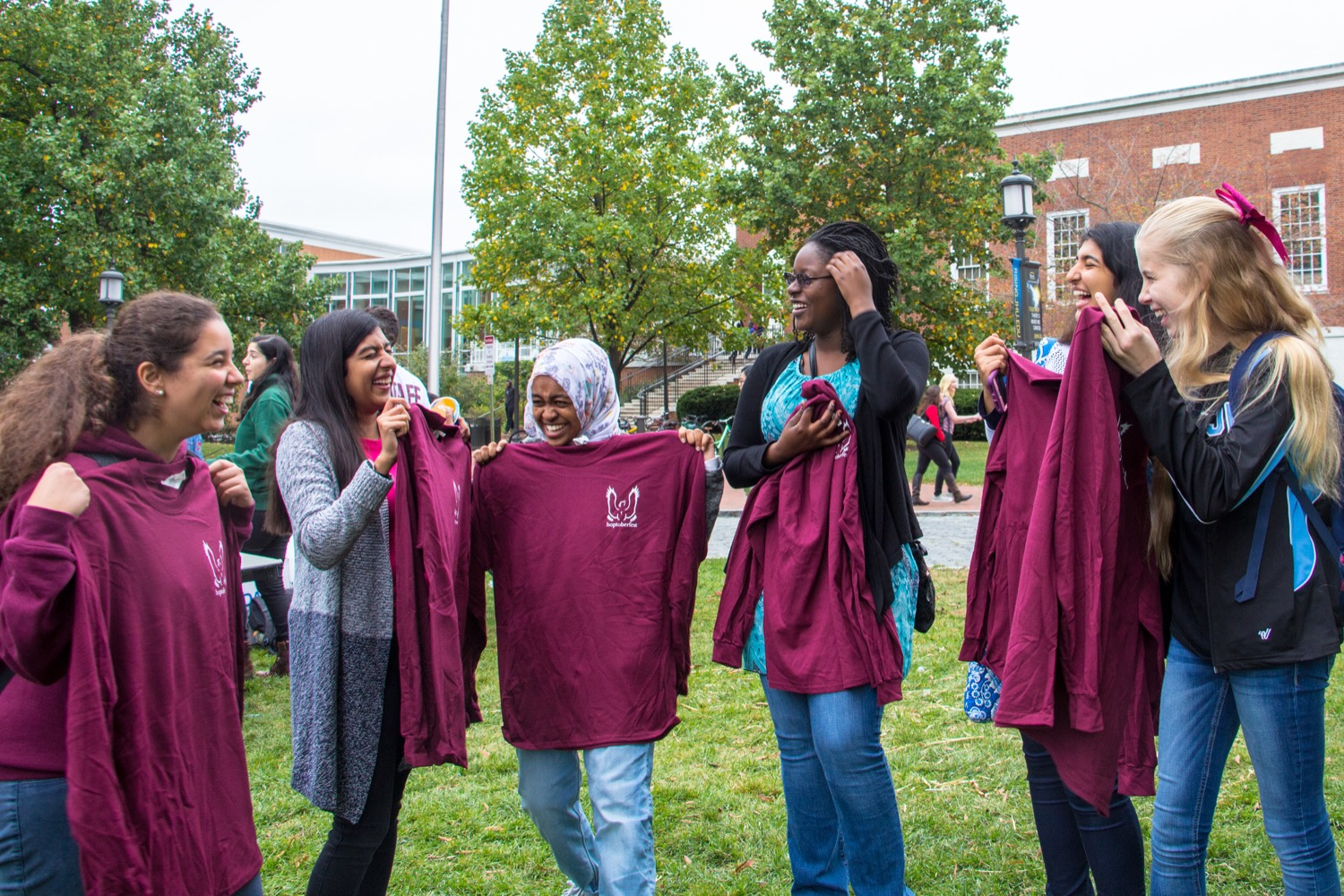 Students smiling, holding up t-shirts