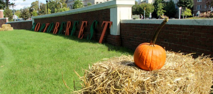 Pumpkin sitting on hay in front of Hoptoberfest sign