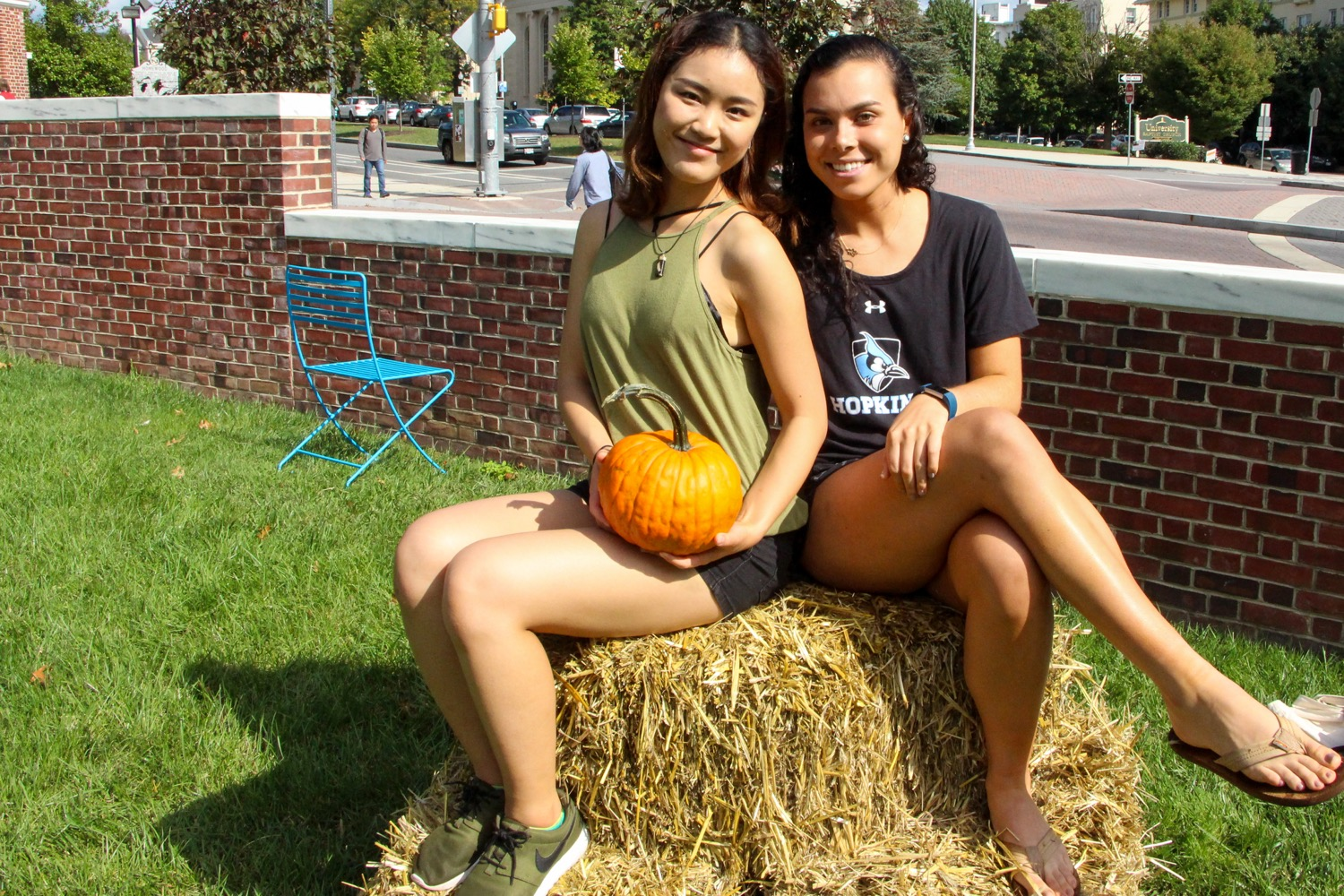 Students seated with pumpkin.