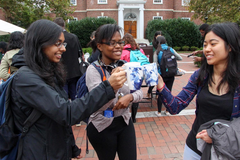 Students holding up mugs