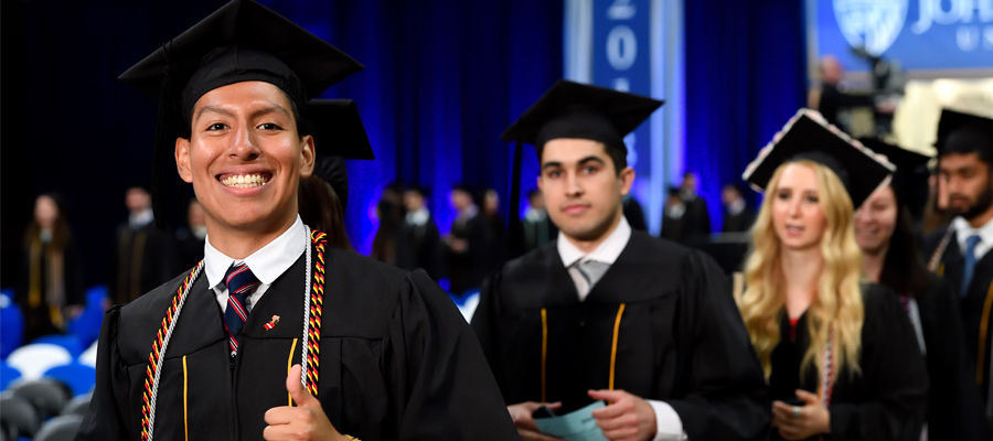 Student giving thumbs up at Commencement