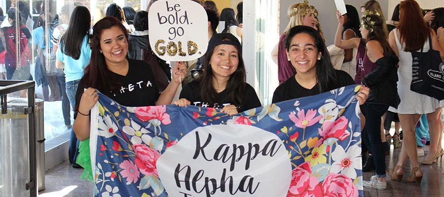 """Women proudly holding banner that reads, """" Kappa Alpha Theta""""."""