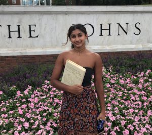 Shanthi standing in front of JHU sign