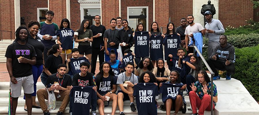 """A group of students gather on the steps to show off their """"I'm First"""" and """"FLI Proud"""" t-shirts."""