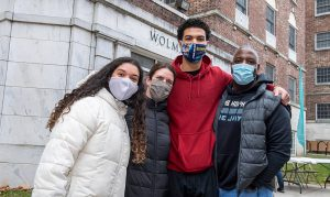 A family wearing masks posing in front of Wolman Hall.