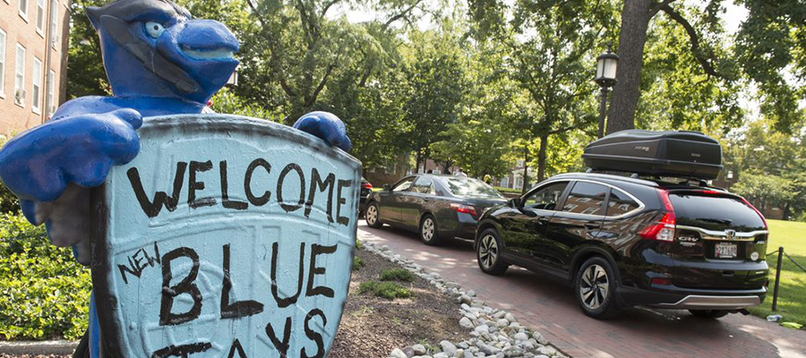 """Blue Jay statue that reads """"Welcome New Blue Jays"""" with a line of cars in the background."""