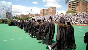 Students line-up on an outdoor field wearing their cap and gowns.