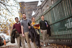 A group of students walk down the city sidewalk past a tall iron fence with fall colored leaves on the ground.