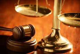 A close up of a weight balance and gavel.