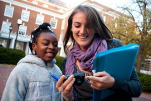 A Hopkins student and a young girl smile while looking at the display of a cell phone.