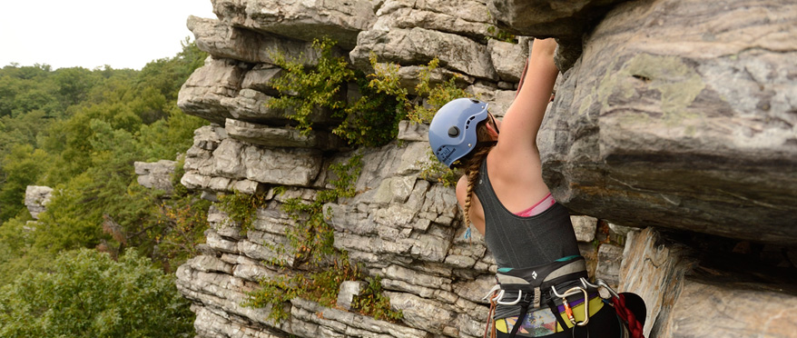 A female climber wearing a helmet and gear, scales the side of an outdoor rock wall.
