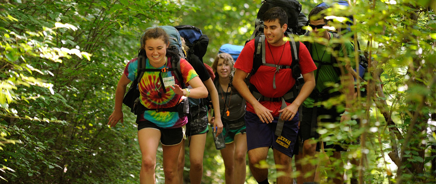 Students hike enthusiastically uphill with backpacks.