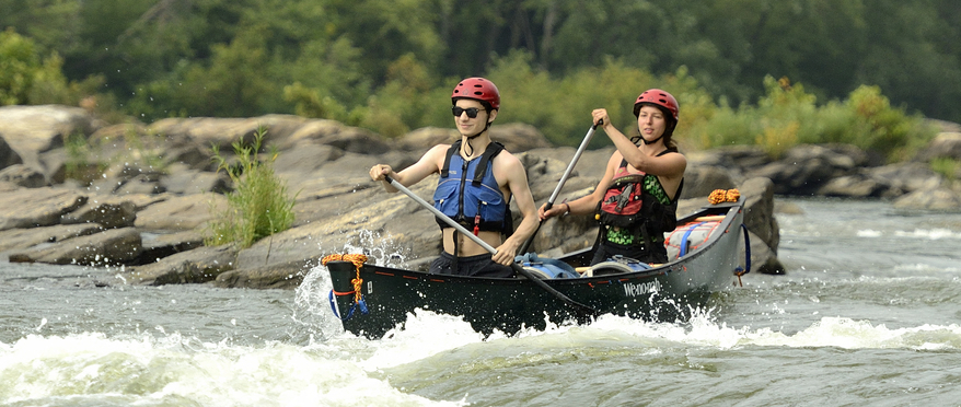 Two students in a canoe maneuver rapid waters.