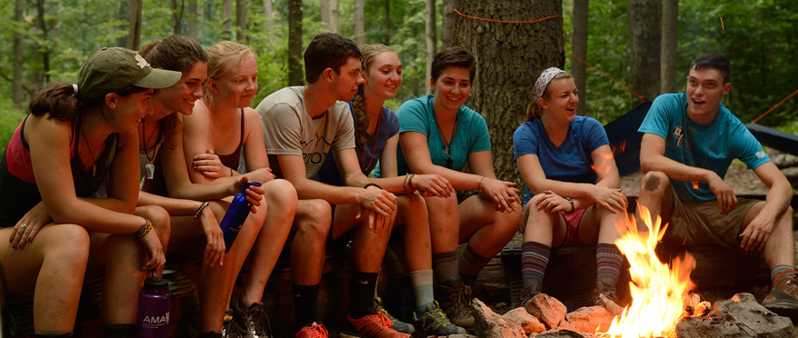 Multiple students sit outdoors on a log in front of a campfire.