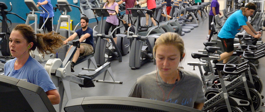 Students running on treadmills in fitness room.