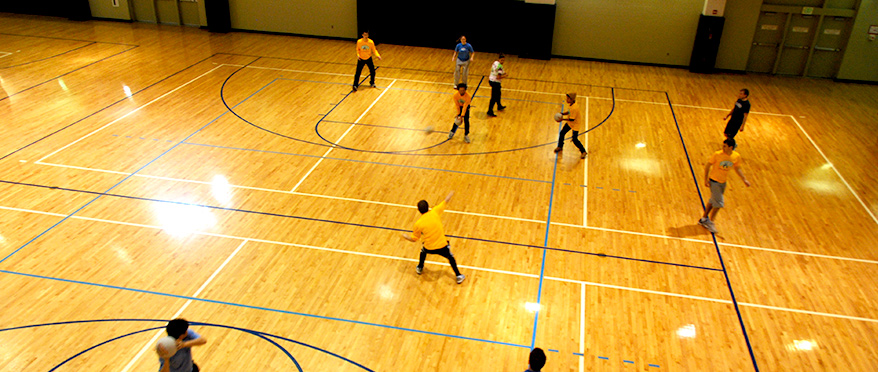 Overhead view of dodgeball game on basketball court.
