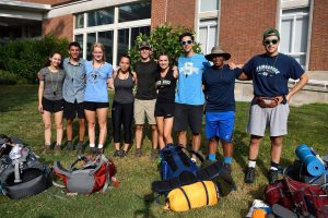 A group of nine first-year students pose for a photo on campus for Outdoor Pursuits