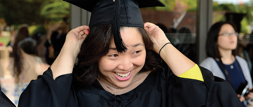 A graduate fixes their cap at Commencement