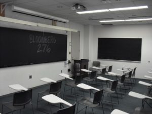Empty classroom showing individual desk and chair seating.