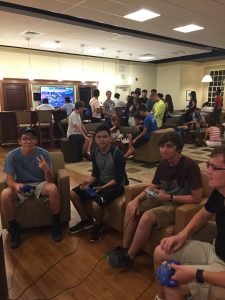 Four students sit in chairs with video controllers in their hands playing together.