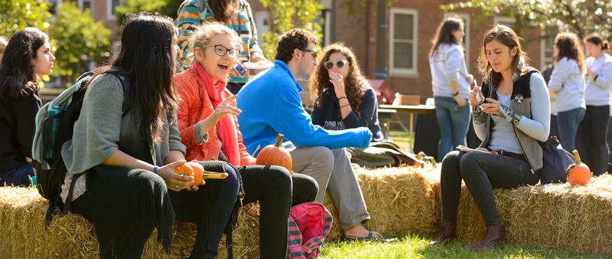 Students sit on hay barrels during hoptoberfest