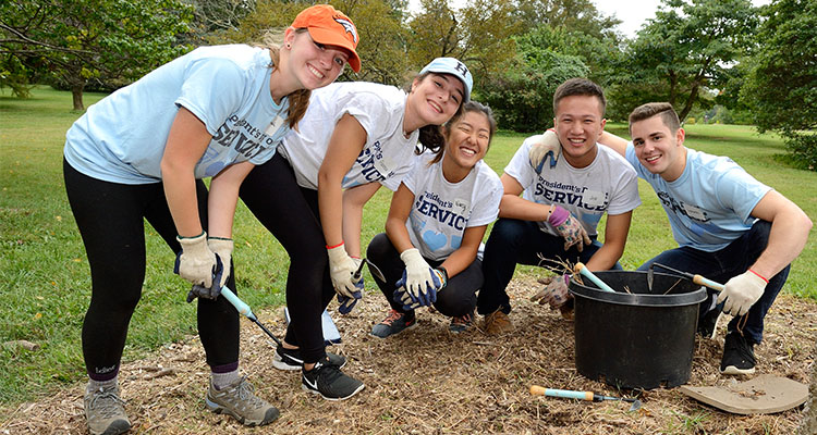 five students posing near tree during president's day of service event