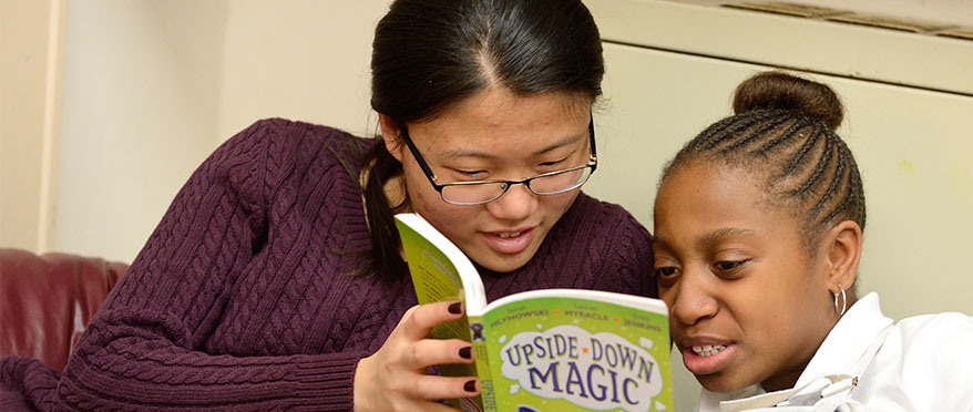 A JHU student leans in closely with a younger, junior high student and together look closely at a book.