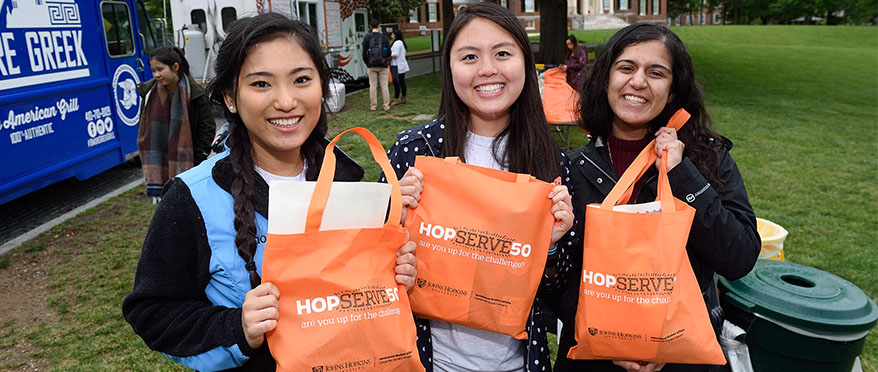picture of 3 girls holding up their hopserve50 swag during the end of year celebration