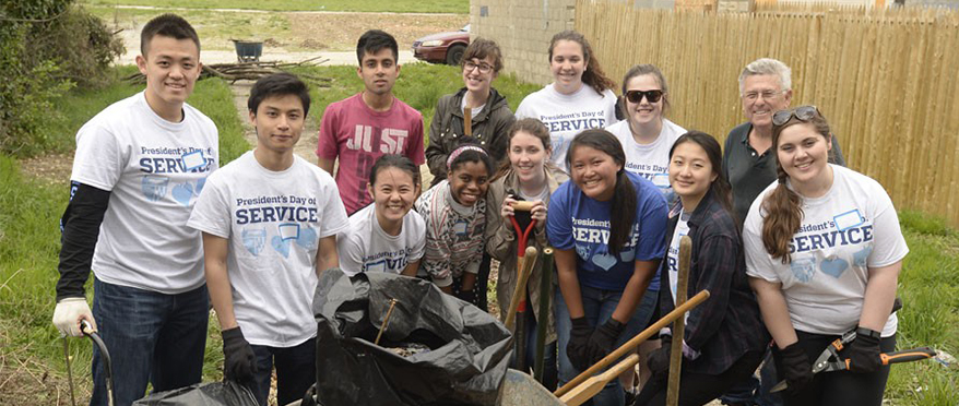 picture of president's day of service volunteers who are cleaning up an outdoor green space