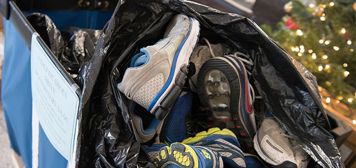 pictures of old sneakers that will be recycled and donated to a nonprofit, Community Recyling