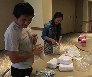 picture of students prepping hygiene kits for donation