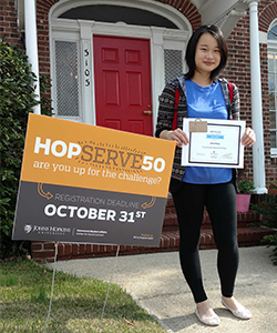photo of Liang Wang in front of Center for Social Concern near HopServe50 lawn sign