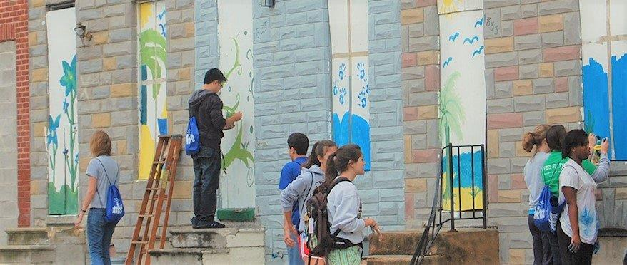 Multiple students standing at multiple boarded up doorways of a row home, painting the exteriors in vibrant colors.