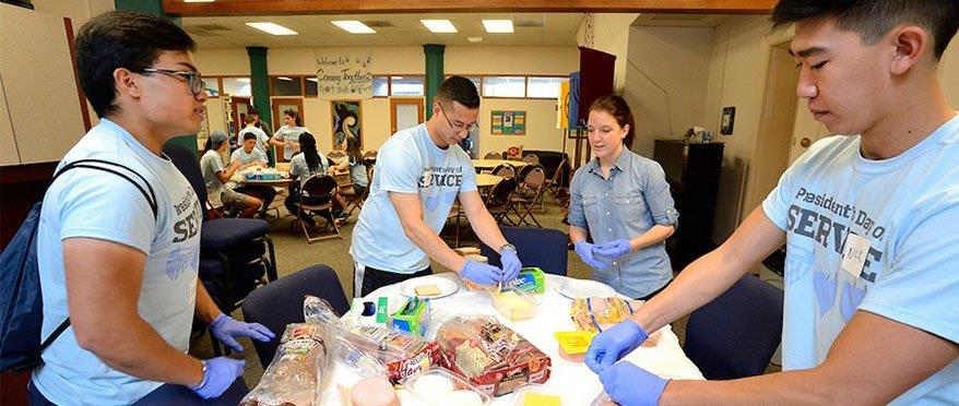 Four students in matching PDOS shirts, prepare sandwiches at a table.