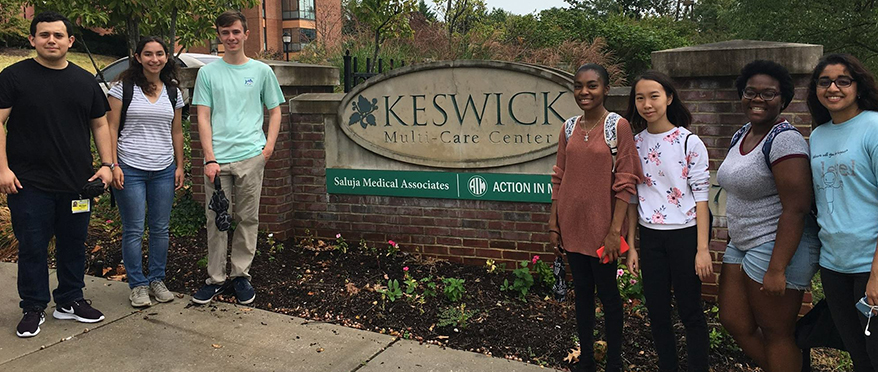 picture of JHU Baltimore First students in front of Keswick Multi Care sign during service