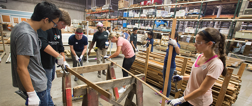picture of a group of JHU students volunteering at second chance by refurbishing building materials