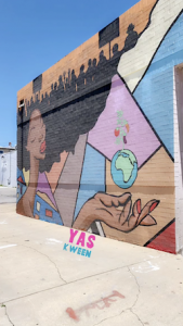 Mural of black girl with afro with the globe in her hand