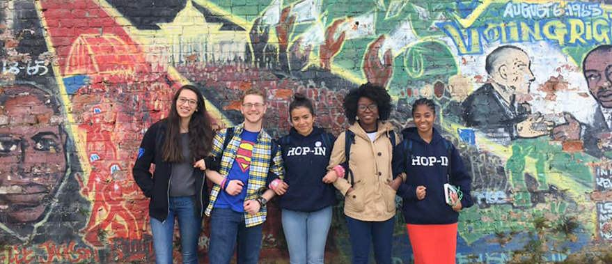 Students pose in front of a mural.