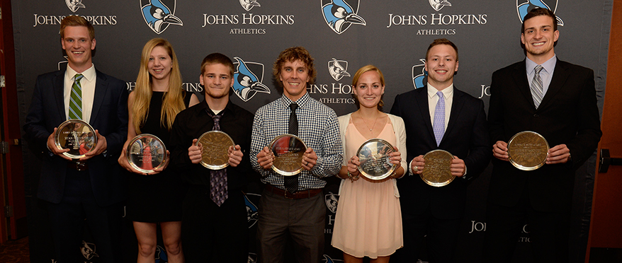 Student athletes holding awards